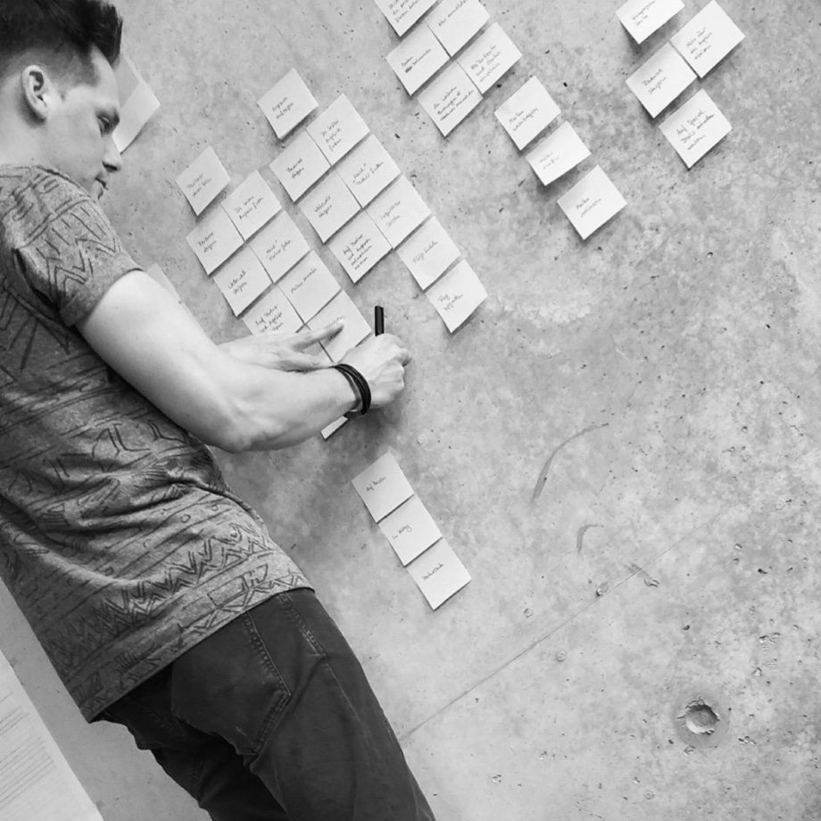 Black-and-white photo of Leander Brasch in front of Post-its on the concrete wall in the office of DUMBO